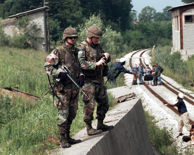 On the afternoon of June 6th, 1996, SSG Jeffrey Fisher (left), Combat Observation Lasing Team (COLT), Platoon Sergeant, 4th Battalion, 29th Field Artillery, 2nd Brigade Combat Team, 1ST Armored Division, Task Force Eagle, stands guard with his M-16A2 rifle over the International Criminal Tribunal for the former Yugoslavia (ICTY). CPT Darren Klemens, 2nd Brigade Combat Team Engineer Officer 1ST Armored Division, Task Force Eagle, is on his left. In the background, members of the Norwegian bomb disposal team prepare to enter a tunnel near the town of Ceparde, Serbsca, during an investigation to find mass grave sites in support of Operation Joint Endeavor
