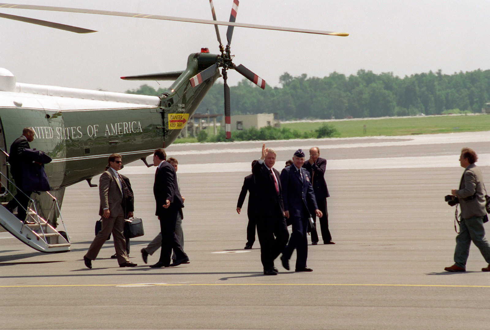 President William Jefferson Clinton waves to spectators as he is escorted from the presidential helicopter, Marince One, to Air Force One by Brigadier General Gary A. Voellger, 437th Airlift Wing commander, Charleston Air Force Base. The president recently returned from Greeleyville, SC after visiting a rural black church that was destroyed by arson a year ago