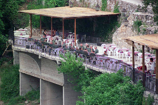 Summertime view of a restaurant along the Neretva river, with several foreign military patrons. Many businesses and cafes have been patched-up or completely refurbished and then restocked. This popular tourist area, surrounding the historic Mostar bridge, has numerous merchant alleys selling hand-crafted items, and cafes with contemporary American music playing. In accordance with the Dayton Accords, under which Operation JOINT ENDEAVOR (the multi-national peace mission in Bosnia) functions, the provision of a secure environment is at the heart of the reconstruction effort in Bosnia