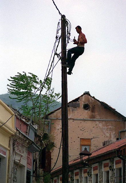 Summertime view of electrical lineman in Mostar. Much of the work available in this region involves some aspect of reconstruction. Most of the rebuilding and fabrication is done by hand or with power tools. Electricity is usually available 24 hr. every day. In accordance with the Dayton Accords, under which Operation JOINT ENDEAVOR (the multi-national peace mission in Bosnia) functions, the provision of a secure environment is at the heart of the reconstruction effort in Bosnia