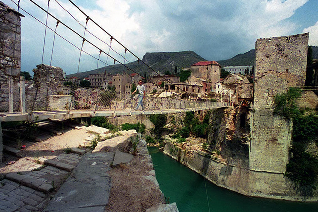 """Summertime view of where the Mostar bridge (1553) was, in Mostar. Since its destruction during the recent civil wars, a temporary footbridge was erected over the span. The Neretva river divides the city, which made the reconstruction and temporary bridges a priority after the cease-fire. Many businesses and cafes have been patched-up and completely refurbished and restocked. This popular tourist area, surrounding the historic Mostar bridge, has numerous merchant alleys selling hand-crafted items, and cafes with contemporary American music playing. It took nine years to build the Mostar bridge over the Neretva river, and it was this bridge which this city named """"The Old Bridge."""" In..."""