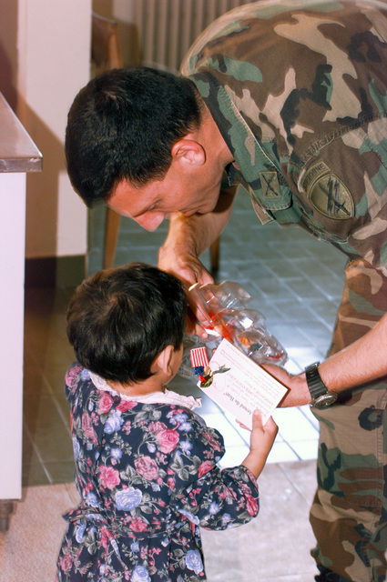 Caption Crowley, US Army, hands some candy to a local girl at an orphanage in Sarajevo Bosnia where Civil-Military Cooperation (CIMIC) Affairs brought toys. Captain Robert Crowley is an Operation Officer with the 352 Civil Military Command out of Fort Meed Maryland, in support of Operation JOINT ENDEAVOR, the multi-national peace mission in Bosnia. The young girl lost her parents in the war in Bosnia