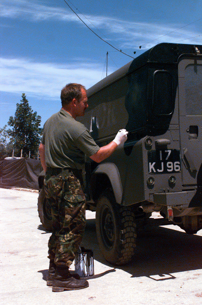 STAFF SGT. White, Radio Communications, 7th Signal Regiment, British Army, repaints his vehicle as part of vehicle maintenance. Allied Rapid Reaction Force Headquarters