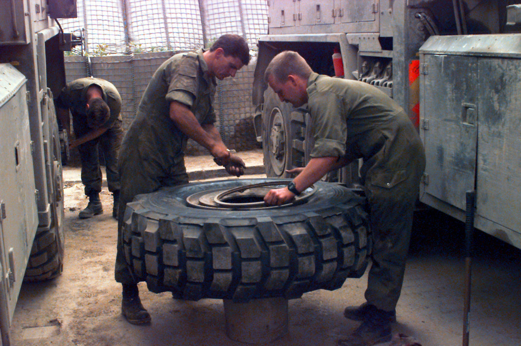 CPL. Bogle and Lance CPL. Towse of the Recovery Section, Light Aid Detachment, 7th Signal Regiment, British Army, replace a tire on a utility vehicle at the Zetra Stadium maintenance facility