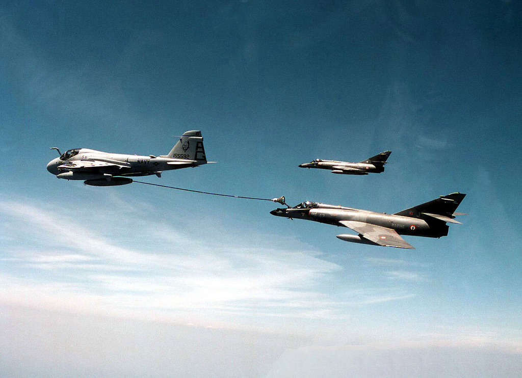 One USN A-6E Intruder, VA-34 Blue Blaster Attack Squadron, refuels a French Navy Dassault Super Etendard fighter bomber, while a second Super Etendard flies along side, in-flight over the western Mediterranean. The A-6E is from the USS GEORGE WASHINGTON (CVN-73) and the Super Etendards are from the French aircraft carrier CLEMENCEAU (R-98). Both carriers are conducting a passing exercise that also includes their respective air wings