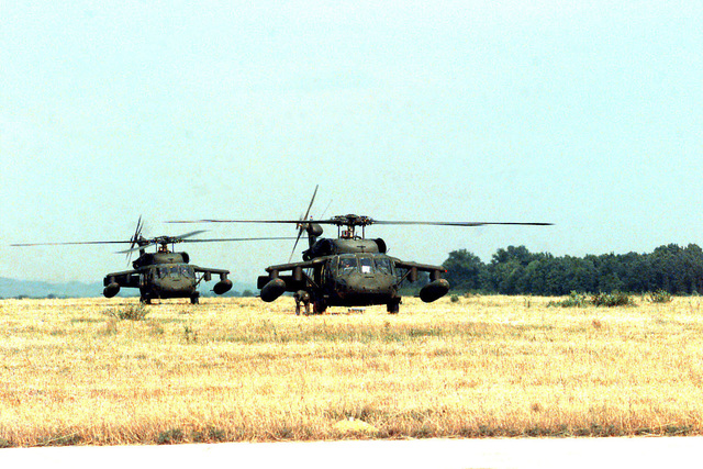 Two parked U.S. Army UH-60 Black Hawk helicopters, B Co., 7/227 Aviation Battalion, are prepared for take-off from a field near an airbase outside of Tuzla (Dubrave), Bosnia-Herzegovina during Operation Joint Endeavor. Operation Joint Endeavor is a peacekeeping effort by a multinational Implementation Force (IFOR), comprised of NATO and non-NATO military forces, deployed to Bosnia in support of the Dayton Peace Accords