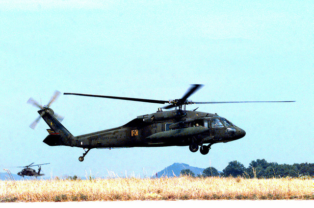 Two U.S. Army UH-60 Black Hawk helicopters, B Co., 7/227 Aviation Battalion, take-off from a field near an airbase outside of Tuzla (Dubrave), Bosnia-Herzegovina during Operation Joint Endeavor. The UH-60 in the foreground has the IFOR marking on the fuselage. Operation Joint Endeavor is a peacekeeping effort by a multinational Implementation Force (IFOR), comprised of NATO and non-NATO military forces, deployed to Bosnia in support of the Dayton Peace Accords