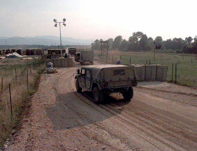 A convoy of three M998 High-Mobility Multipurpose Wheeled Vehicles (HMMWV), one M1038 HMMWV, and one transport truck enter the main gate at Steel Castle Base (CQ258252), Bosnia-Herzegovina. The US forces are in Bosnia in support of Operation Joint Endeavor. Operation Joint Endeavor is a peacekeeping effort by a multinational Implementation Force (IFOR), comprised of NATO and non-NATO military forces, deployed to Bosnia in support of the Dayton Peace Accords