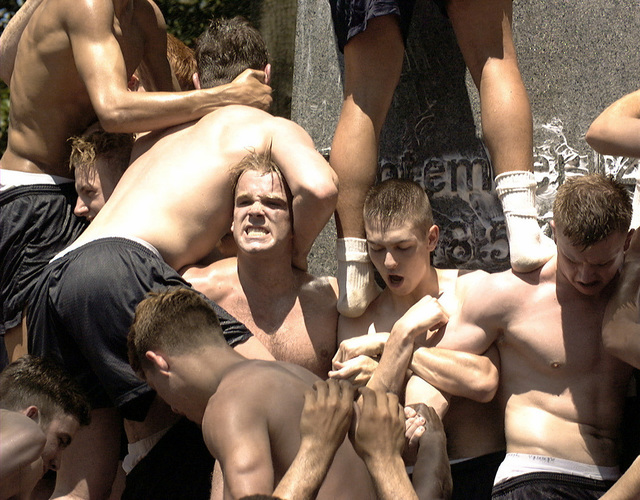 """Plebes (freshmen) work together to scale the lard covered Herndon monument, a 21-foot obelisk, to replace a sailor's cap (""""dixie cup"""") with an upper classman's cap. After the climb, the plebes will be referred to as fourth classmen"""