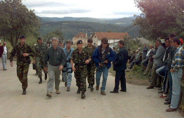 The Honorable Walter B. Slocombe (gray shirt), Under Secretary of Defense (Policy), his security personnel, and several unidentified soldiers walk along a road, lined by Croatian civilians, that runs through Cukuvi, Bosnia-Herzegovina. Mr. Slocombe is on a two-day visit to Bosnia-Herzegovina to meet with IFOR personnel and various Bosnian civic leaders