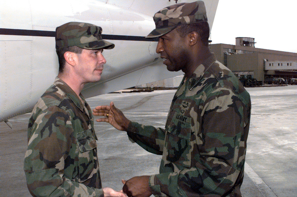 Sergeant Major of the Army, Gene McKinney, hands STAFF Sergeant Koley Scott a coin before leaving Sarajevo