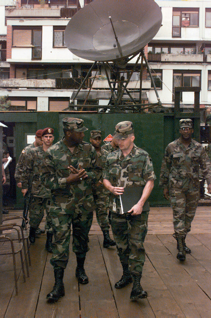 Sergeant Major of the Army, Gene McKinney, walks and talks with Sergeant First Class Randolph Anglin at the 44th Signal Company site located at the Residency in Sarajevo. Other team members including the security guards and twin brother, Command Sergeant Major James McKinney follow behind. A large sattelite dish can be seen on top of the building in the background