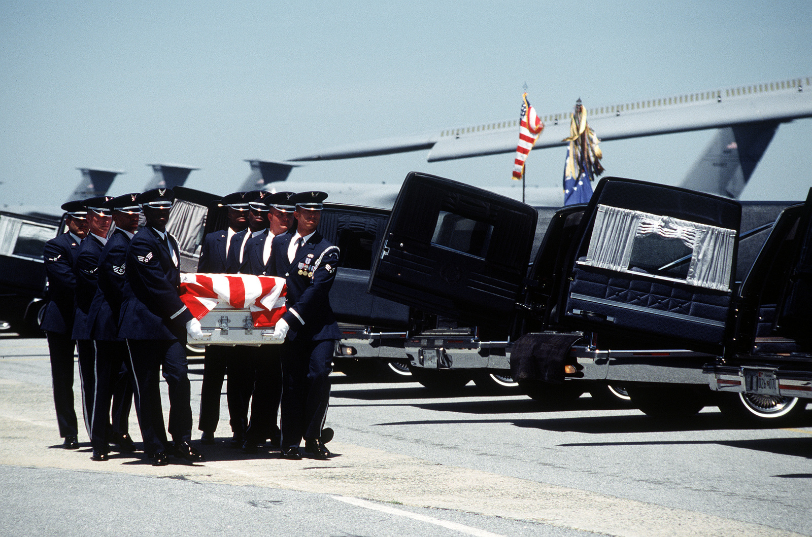 Dover Air Force Base honor guard carries the flag draped casket of one of the nineteen service members killed in the Dhahran, Saudi Arabia bombing. A memorial service for the nineteen military members is being held on the flightline at Dover Air Force Base, Delaware on June 27, 1996