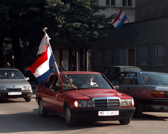 An automobile decorated with a flag and streamers is participating in a parade through the streets on the eve of the Mostar General Elections