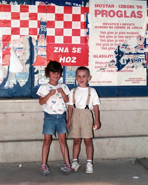 Croatian children pose in front of numerous campaign posters on a western Mostar street on the eve of the Bosnian national general elections
