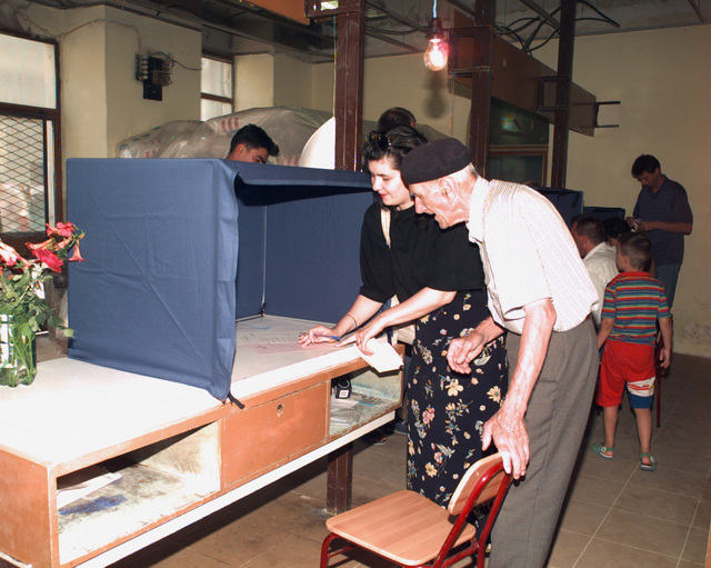 A citizen voter is helped in filling out his ballots by a family member at one of the many polling locations on the day of the Mostar general elections