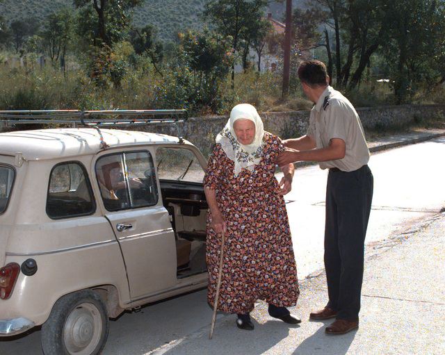 A Federal police officer assists a Bosnian citizen in making her way to the Blagaj polling location so that she may place her vote in the Mostar general elections