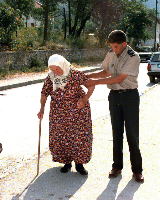 A Federal police officer assists a Bosnian citizen towards the Blagaj polling location so that she may place her vote on the day of the Mostar general elections