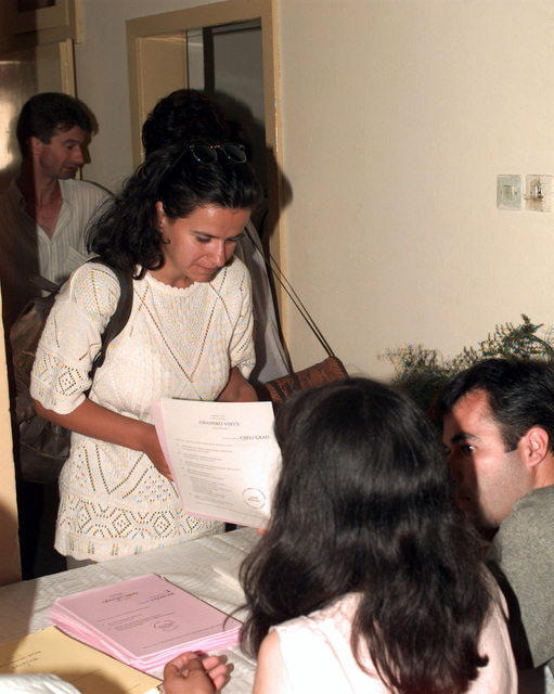 A Muslim citizen receives her ballots from an election official at the Blagaj polling location after presenting the proper registration identification