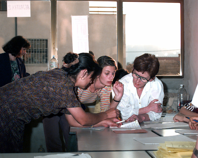 Ballots being tabulated by election officials while a European Nations impartial observer looks on after the completion of the Mostar general elections at the Bejrut polling station