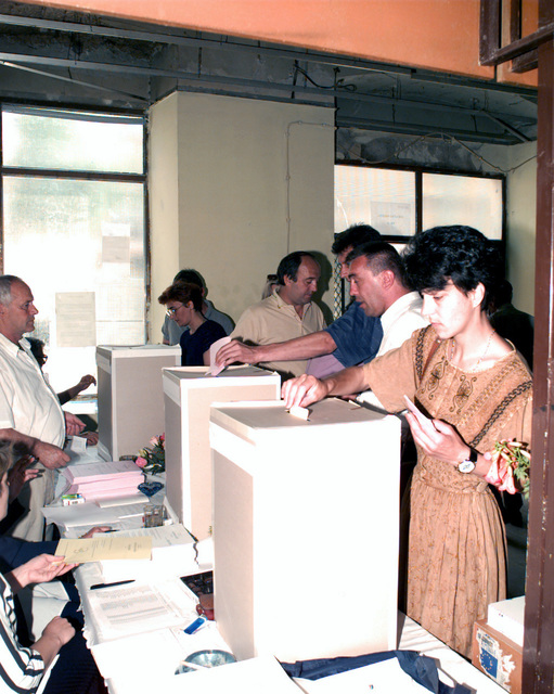 Bosnian voters place their filled out ballots into their respective collection boxes at one of the many polling locations in eastern Mostar on the day of the Mostar general elections