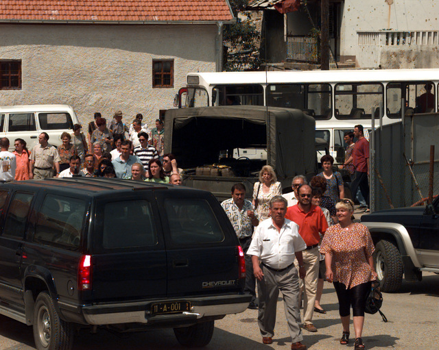 Displaced Bosnian voters exit a transport bus and move towards the Bejrut polling location in eastern Mostar so that they might place their votes in the area that they were registered to vote in during the Mostar general elections