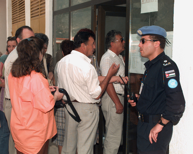 Prospective citizen voters enter the Bejrut polling location on the day of the Mostar general elections while a security guard stands at the entrance to prevent incidents
