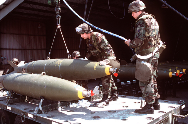 AIRMAN Shawn Tubbs (left) and SENIOR AIRMAN Mike Fernandez, 35th Munitions Squadron, Misawa AB, Japan, load a trailer with MK-84 low drag bombs during this combat ammunition production exercise.Published in AIRMAN Magazine July 1996. Exact Date Shot Unknown