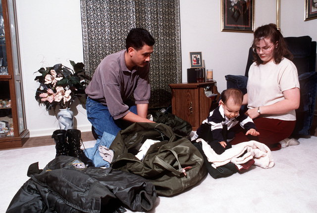 SENIOR AIRMAN Chris and Michelle Kimber pack for Chris' next deployment while son, Alexander, plays.Published in AIRMAN Magazine July 1996. Exact Date Shot Unknown