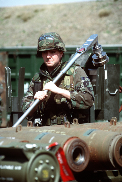 SENIOR AIRMAN Chris Nichols, 35th Munitions Squadron, Misawa, AB, Japan, shoulders a massive torque wrench used to assemble GBU-12 bombs during this combat ammunition production exercise.Published in AIRMAN Magazine July 1996. Exact Date Shot Unknown