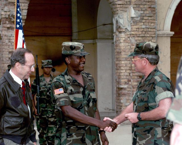 The Secretary of Defense, the Honorable William J. Perry, watches as the Commander of IFOR, Admiral Leighton Smith, congratulates Brigadier General Voneree Deloatch, commanding officer of the Civil Military Cooperation Detachment (CIMIC), just after his promotion at the Allied Command Europe Rapid Reaction Corps Headquarters in the Sarajevo suburb of Ilidza. (Duplicate image, see also DASD9903191 or search 960703A8303M006)