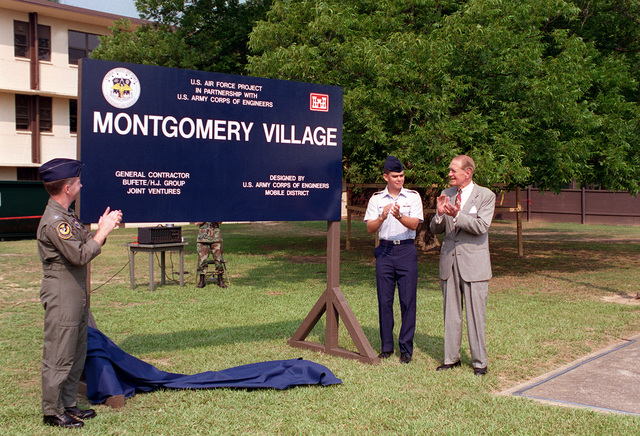 Congressman Montgomery and two Air Force officers applaud as the sign marking the site of the future dormitory complex is unveiled