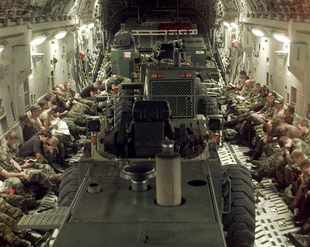 Inside the cargo hold of the C-17, the equipment occupies the center and the Hurricane Response Force personnel sit on the seats lining the sides. They are enroute from McGuire Air Force Base, New Jersey to Charleston Air Force Base, South Carolina to assist with any damage caused by Hurricane Bertha