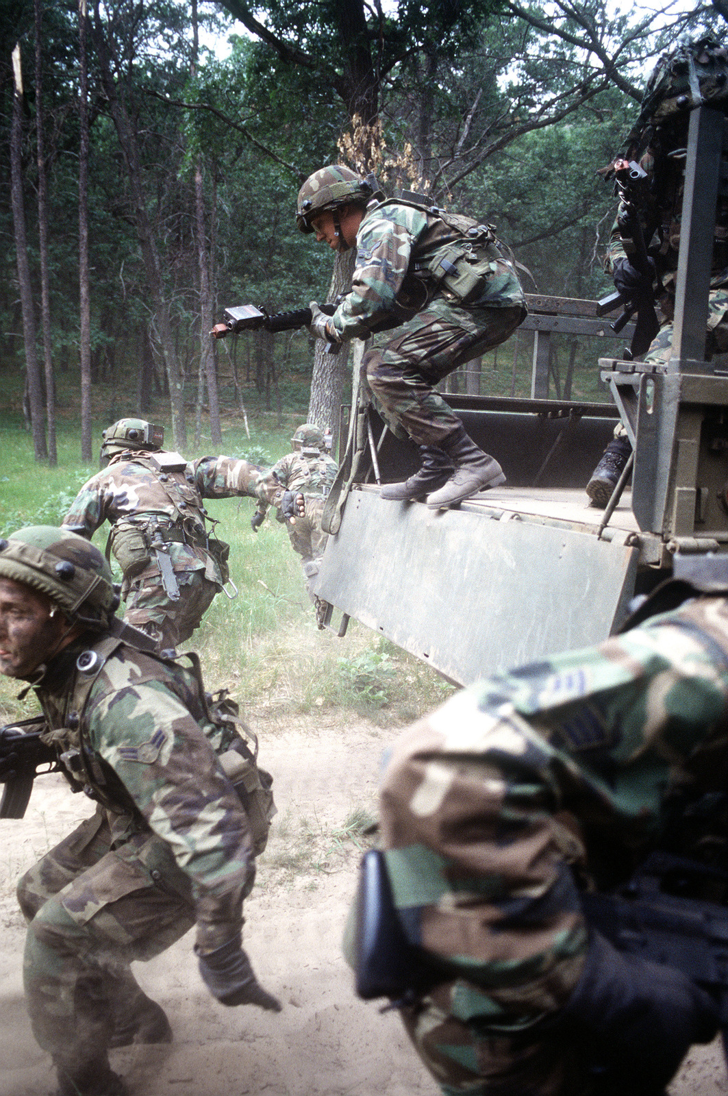 "At the Volk Field Combat Readiness Training Center, a surprise attack by ""aggressor"" forces causes the base defenders, in full combat field gear, to abandon their vehicle during a convoy, and take up defensive positions as part of their Air Base Ground Defense training (ABGD)"
