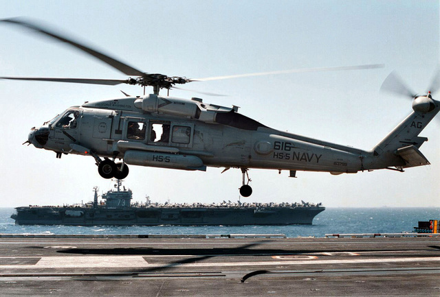 """An SH-60H Seahawk helicopter from the """"Nightdippers"""" of Helicopter Antisubmarine Squadron Five (HS 5) touches down on the deck of aircraft carrier USS ENTERPRISE (CVN 65) during turnover operations with the USS GEORGE WASHINGTON (CVN 73) (background) in the western Mediterranean Sea. George Washington is nearing completion of her second scheduled deployment since her commissioning, while the Enterprise returns to sea for her first scheduled deployment in several years"""