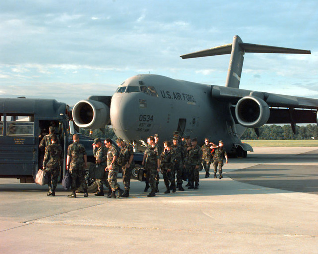 Members of the Hurricane Response Force deplane from the C-17 Globemaster III and board a waiting bus upon arrival. The sunny weather indicates that Hurricane Bertha has not hit the base. SCREEN RESOLUTION ONLY