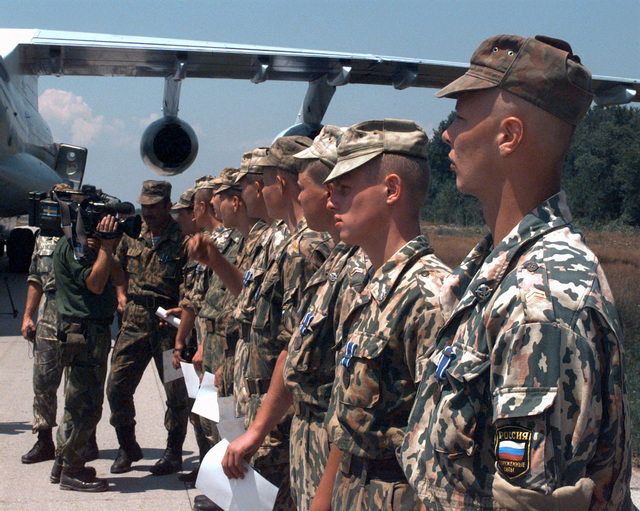 Outgoing Russian Airborne troops are interviewed by documentation specialists from the Nord - Pole Brigade after receiving the NATO medal from Major General William L. Nash, Commanding General of Task Force Eagle, during an informal ceremony held on the airfield at Tuzla Air Base Bosnia - Herzegovina in Task Force Eagle during Operation JOINT ENDEAVOR (the multi-national peacekeeping mission in Bosnia). The soldiers received the medal after spending six months at various locations within the Russian Brigade area