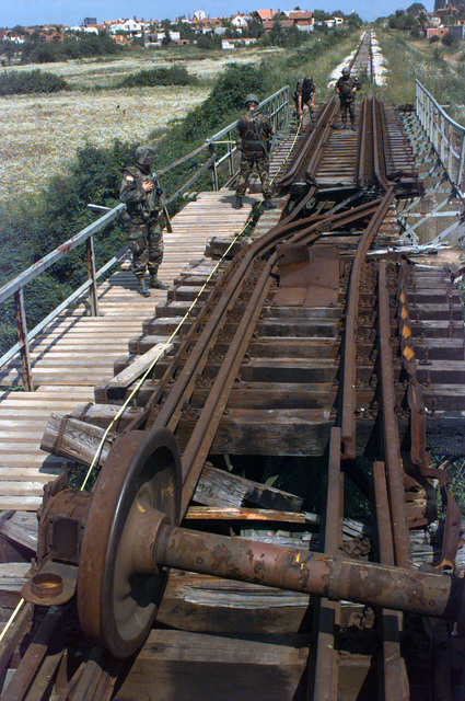 Captain Guiseppe Benetti, CHIEF Arturo Castella (right, background) and SSGT Pasquale Galami (left, background), 1ST Battalion, Italian Railway Engineer Regiment, and US Captain Gina Casselberry (foreground) 422nd Civil Affairs Battalion supporting 23rd Engineer Battalion conduct a site survey of the Kolonija Rail Bridge for future reconstruction in support of Operation JOINT ENDEAVOR (the multi-national peacekeeping mission in Bosnia)