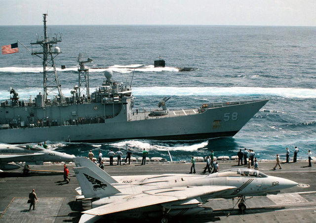 A view from onboard the US Navy (USN) NIMITZ CLASS: Aircraft Carrier, USS GEORGE WASHINGTON (CVN 73), showing flight deck personnel and aircraft on deck, as the USN OLIVER HAZARD PERRY CLASS: Guided Missile Frigate, USS SAMUEL B. ROBERTS (FFG 58) (middle ground), and the USN LOS ANGELES CLASS: Attack Submarine USS BALTIMORE (SSN 704) sail in a battle group formation, while returning to homeport, following a scheduled six-month deployment