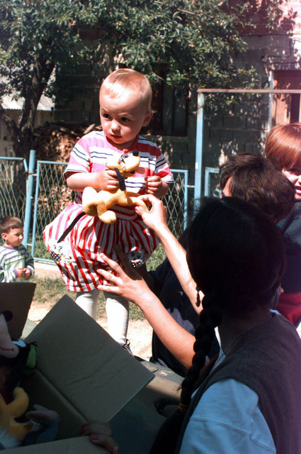 A child from the village of Hadzici, Bosnia and Herzegovina, receives a stuffed animal from the Civil Military affairs (CIMIC) along with Samaritans Purse, a civilian relief group. The two came together to distrubute Disney toys and candy to the children in the village during Operation JOINT ENDEAVOR