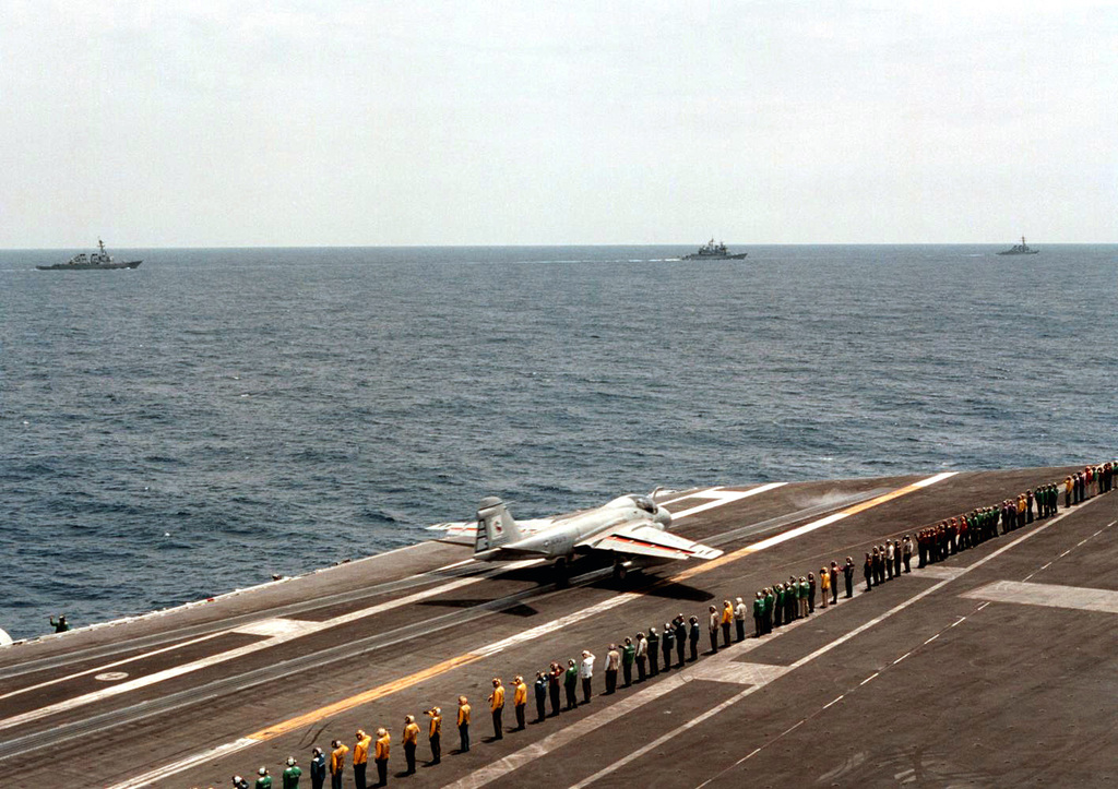"""Attack Squadron Three Four (VA-34) aircraft number 500"""", the last A-6E Intruder aircraft launched from the flight deck of the US Navy aircraft carrier USS GEORGE WASHINGTON (CVN 73), accelerates down catapult number three. Crewmen from the ships aircraft launch and recovery equipment division line the deck to salute the aircraft as it launches. Governor George Allen of Virginia (not shown), who was on board the George Washington to welcome her crew back after the successful completion of her six-month deployment, launched the Intruder on its historic flight. This was the final deployment for VA-34 flying the Intruder aircraft. The squadron will begin training on the F/A-18C Hornet ..."""