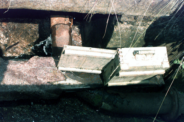 """Using the box as a marker, a """"pineapple"""" anti-personnel mine was planted approximately three feet away from the break in the water line at the Rajlovak train facility, located on the outskirts of Sarajevo, Bosnia and Herzegovina, during Operation JOINT ENDEAVOR. The owner of the facility said that he pays more for the water than he pays for the salary of all his workers. He has been asking for 3 months to get it removed, but the Mine Action Center (MAC) is low on funding, and cant remove the mine"""
