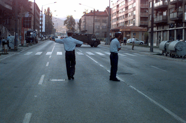 Civilian police redirect traffic for a demonstration that is taking place at the main intersection in downtown Sarajevo, Bosnia and Herzegovina, during Operation JOINT ENDEAVOR. The demonstration is directed to compensate soldiers who were disabled during the war in Sarajevo