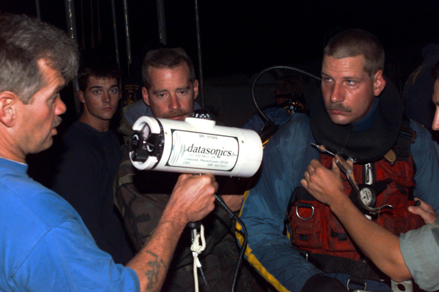 "US Navy Hull Technician 1ST Class Patrick Wheeler (right) listens to last-minute instructions on the ""pinger locator"" before starting his next dive. Wheeler is assigned to the submarine tender USS EMORY S. LAND (AS 39), and is diving from the Navys salvage rescue ship USS GRASP (ARS 51) as part of an augmentation force to facilitate 24-hour diving operations. US Navy Boatswains Mate CHIEF Donald Dennis, stationed aboard the Grasp, displays the Datasonics ""pinger locator"", used to locate Remote Operated Vehicles (ROVs). The ROVs role in finding bodies from the crash of TWA flight 800 has been a tremendous asset for his divers responsible for a gruesome yet important task. Instead of ..."