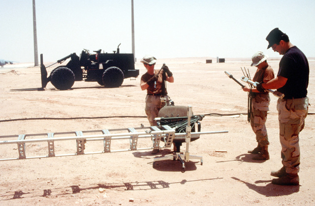 TECH. SGT. Harry Anson, 1ST LT. Lisa Lau and TECH. SGT. Patty Sylin, all from the 615th Air Mobility Control Squadron, Travis Air Force Base, California, are setting up the Ultra High Frequency (UHF) ground to air antenna for the nerve center, Tanker Air Lift Control Element (TALCE). This facility will control all aircraft movements in and out. This is the relocation of Operation Southern Watch from Dhahran after a terrorist bomb killed 19 Air Force personnel in June