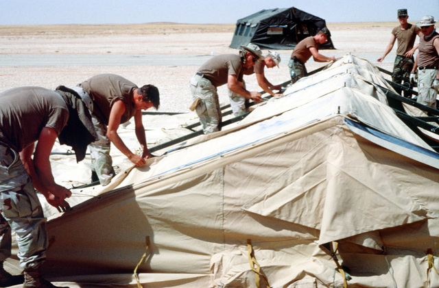Members of the 823rd Red Horse Squadron from Hurlbert Field Florida and the 49th Material Maintenance Group from Holloman Air Force Base New Mexico build one of 500 tents to house upwards of 4,000 personnel in support of the relocation of Operation Southern Watch