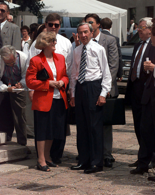 Secretary of State Warren Christopher (not wearing a coat) and the Republic of Srpska Provisional President Biljana Plavisic (the woman in the red suit jacket) stand next to each other, in front of other civilians, on a street in the historic old town section of Sarajevo, Bosnia-Herzegovina. Secretary Christopher is visiting Bosnia to check on the peace process progress and the status of the upcoming elections