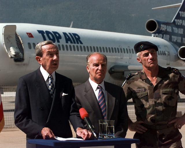 Secretary of State Warren Christopher, standing next to Bosnia-Herzegovinian President Alija Izetbegovic and Deputy Commander IFOR LGEN Jean Heinrich (French Army), speaks from behind a lectern located on the tarmac at the Sarajevo International Airport about reopening the airport to civilian traffic. A TOP AIR commercial aircraft is seen in the background. Secretary Christopher is visiting Bosnia to check on the peace process and the status of the upcoming elections