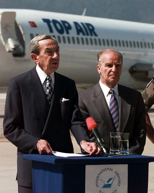 Secretary of State Warren Christopher, standing next to Bosnia-Herzegovinian President Alija Izetbegovic, speaks from behind a lectern located on the tarmac at the Sarajevo International Airport about reopening the airport to civilian traffic. A TOP AIR commercial aircraft is seen in the background. Secretary Christopher is visiting Bosnia to check on the peace process and the status of the upcoming elections