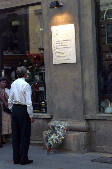 Secretary of State Warren Christopher stands and looks at a plaque, attached to a wall, that honors the fallen victims of the bombings that occurred on 27 June 1992 in the marketplace in Sarajevo, Bosnia-Herzegovina. Secretary Christopher is visiting Bosnia to check on the peace process progress and the status of the upcoming elections